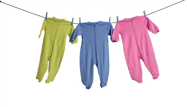 Baby sleepers on the clothesline, studio isolated on white.